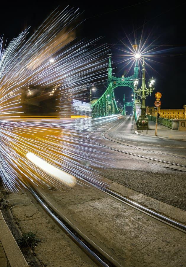 Budapest Ungern - den Festively dekorerade ljusa spårvagnen Fenyvillamos på flyttningen på Liberty Bridge Szabadsag dolde vid nat royaltyfri foto