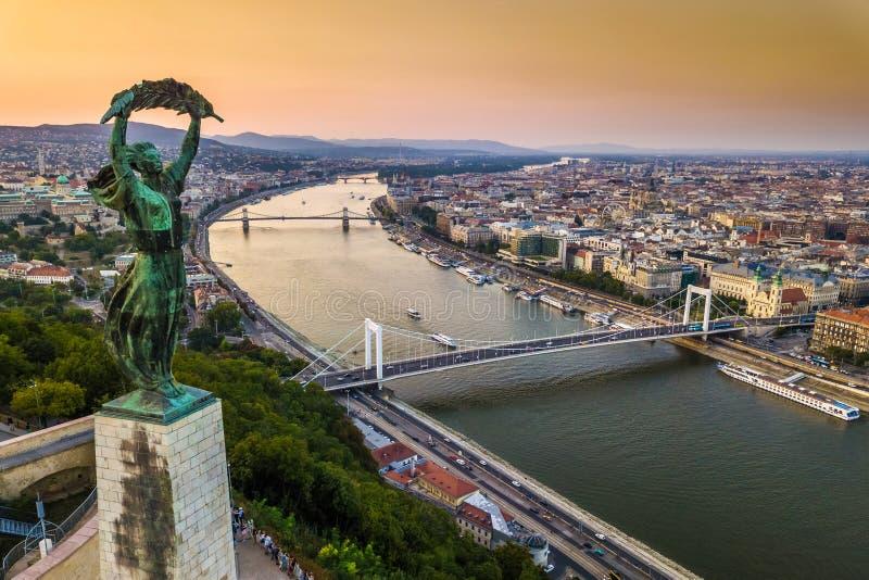 Budapest Ungern - den ungerska statyn av frihet på soluppgång med Elisabeth Bridge och Szechenyi den Chain bron royaltyfria foton