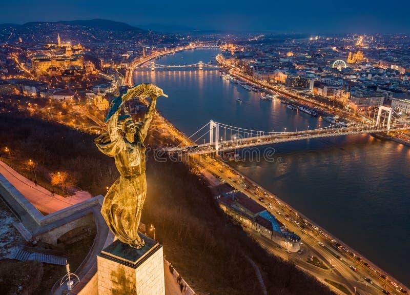 Budapest Ungern - flyg- blå timmesikt av den upplysta statyn av frihet med Elisabeth Bridge, Buda Castle Royal Palace royaltyfri bild