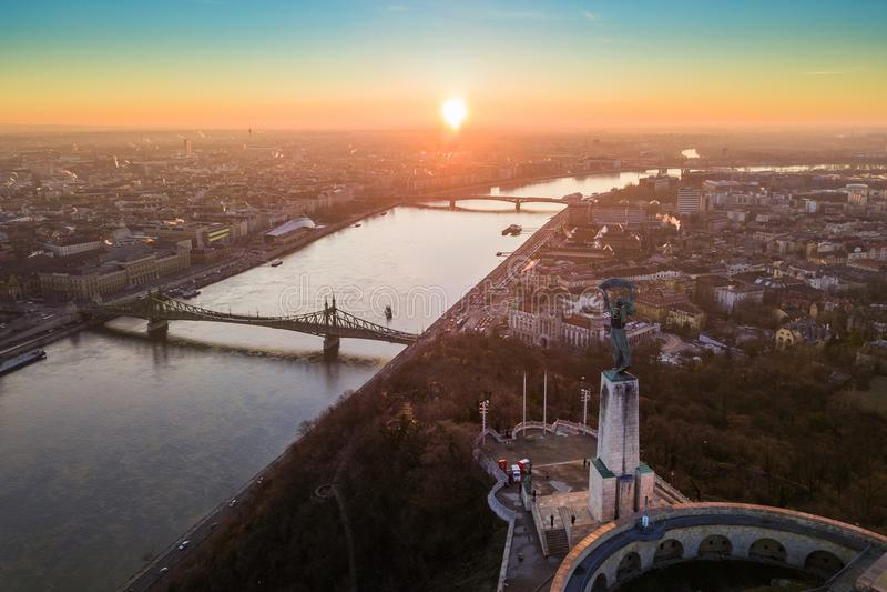 Budapest Ungern - flyg- panorama- soluppgångsikt på statyn av frihet med Liberty Bridge och sightfartyg arkivbild