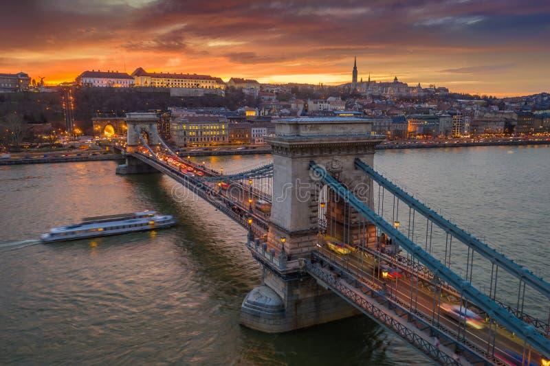 Budapest Ungern - flyg- sikt av den berömda Szechenyi kedjebron med en härlig guld- solnedgång på vintertid arkivbild