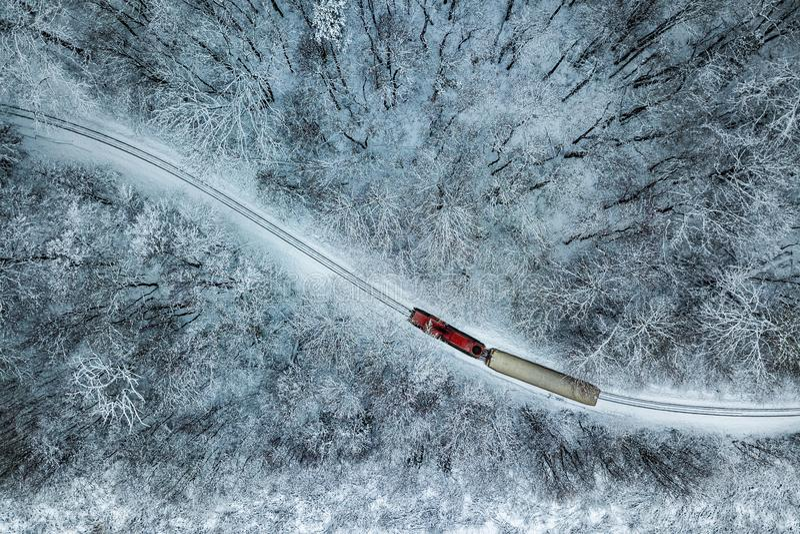 Budapest Ungern - flyg- sikt av den snöig skogen med det röda drevet på ett spår på vintertid royaltyfri bild