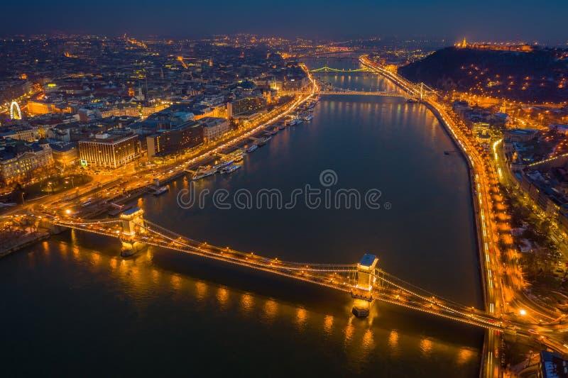 Budapest Ungern - flyg- sikt på den blåa timmen av den Szechenyi kedjebron, Elisabeth Bridge och staty av frihet royaltyfri bild