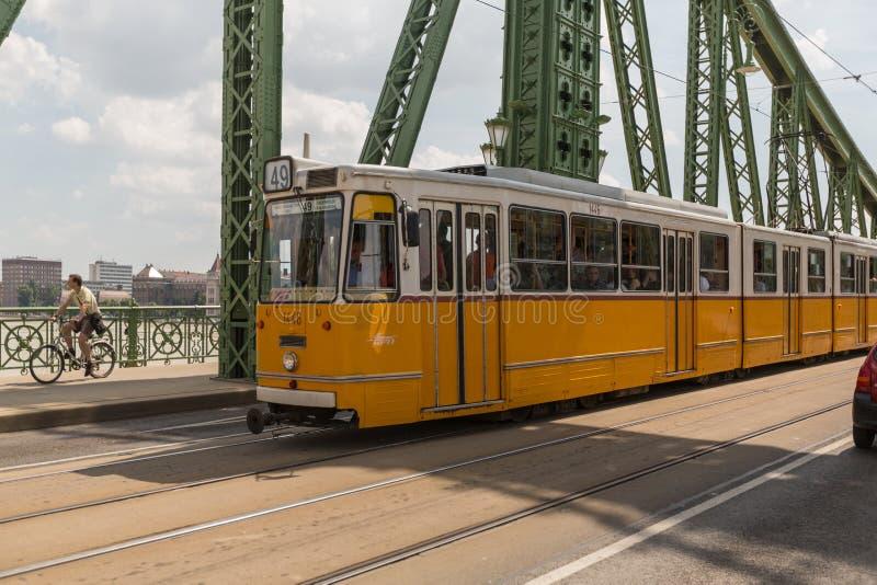 BUDAPEST UNGERN - JUNI 10, 2014 - spårvagnen på frihetbron med den gamla saluhallen på bakgrunden, på Juni 10, 2014 i knopp royaltyfri foto