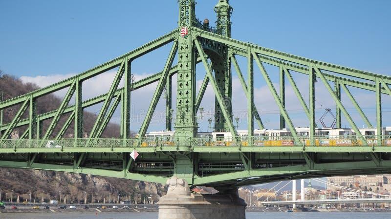 Budapest Ungern Liberty Bridge eller frihetsbron ?ver flodDonauen Den gula sp?rvagnen rider p? bron arkivbild