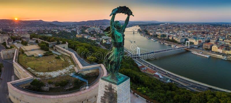 Budapest Ungern - panoramautsikt av den ungerska statyn av frihet på soluppgång med Elisabeth Bridge och Szechenyi den Chain bron royaltyfri foto