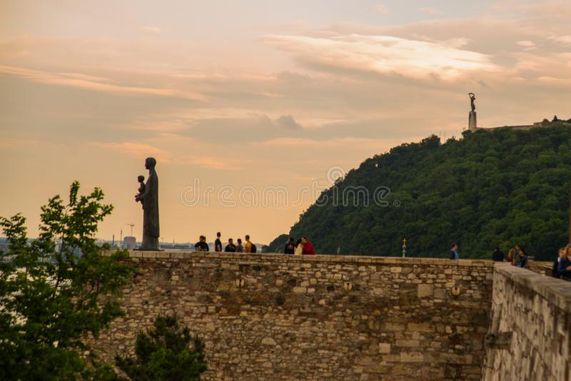 Budapest Ungern: Skulpturen av St Maria Mater Dei på kulleöverkanten av Buda Castle Liberty Statue eller frihetsstatyställningar  royaltyfri foto
