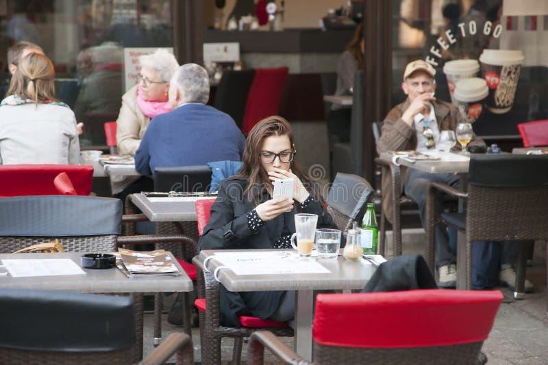 Budapest, Ungheria - 8 aprile 2018: La bella ragazza redige un messaggio di testo sul vostro telefono mentre si siede in caffette immagine stock libera da diritti