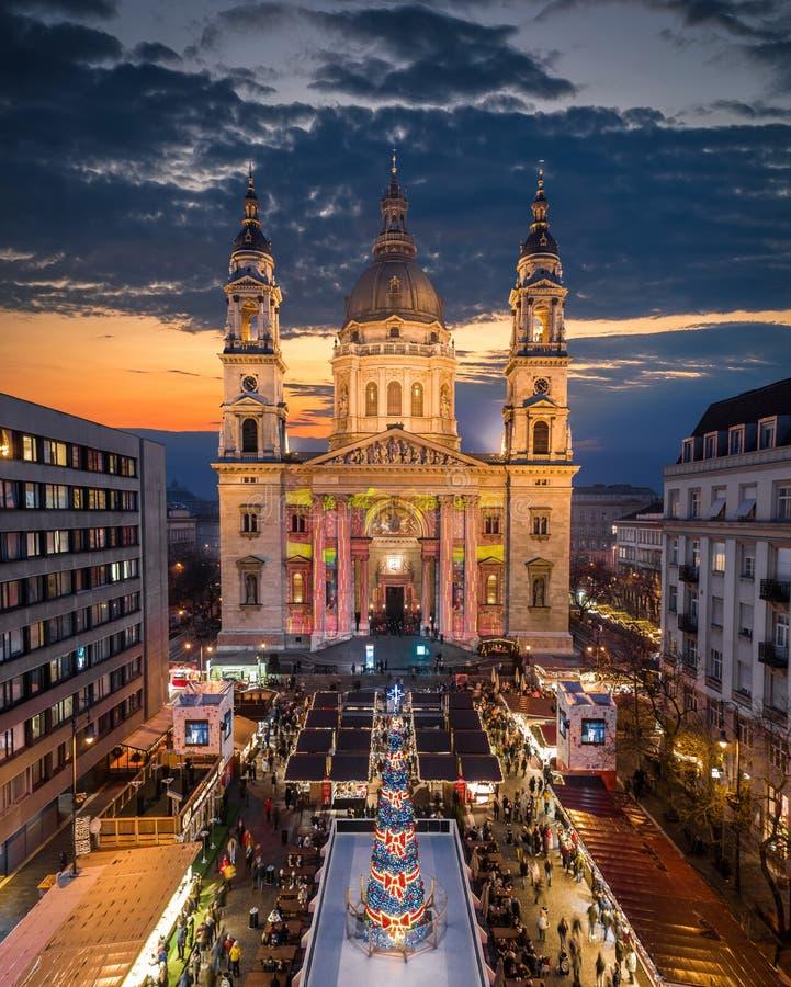 Budapest, Ungheria - una visione aerea dei droni del più bel mercato natalizio europeo con l'illuminata Basilica di Santo Stefano immagini stock