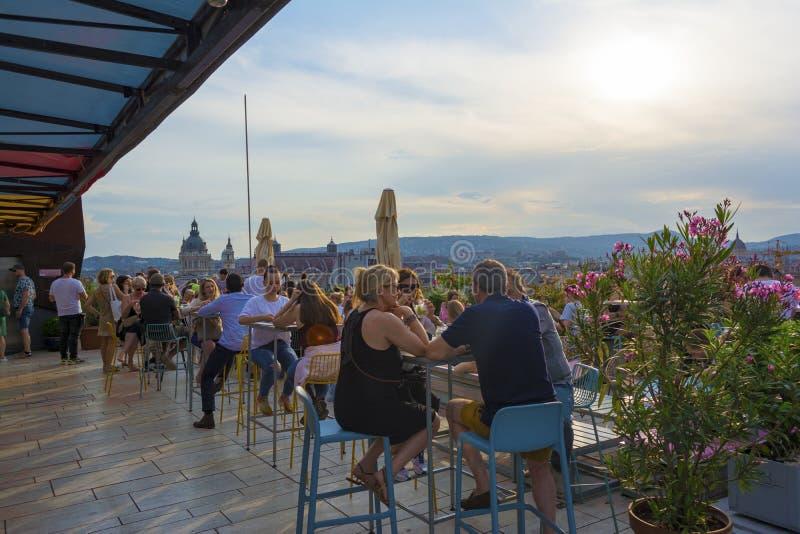BUDAPEST WĘGRY, MAJ, - 12, 2018: Ludzie są pijący i opowiadający each inny przy dachu barem z pięknym zdjęcia stock