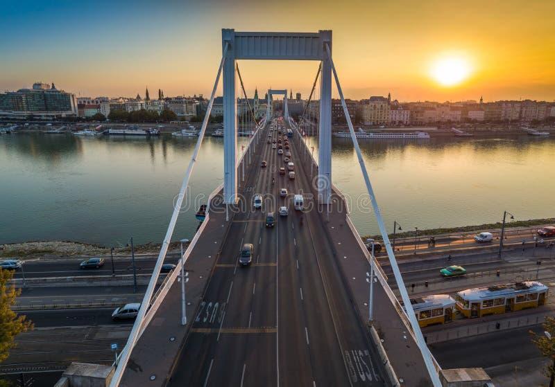 Budapest, Węgry - Piękny Elisabeth most Erzsebet chował przy wschodem słońca z złotym i niebieskim niebem, tradycyjny żółty tramw zdjęcia stock
