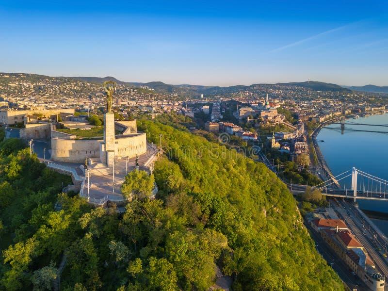 Budapest, Węgry - Powietrzny linia horyzontu widok statua wolności na Gellert wzgórzu przy wschodem słońca z jasnym niebieskim ni obrazy stock