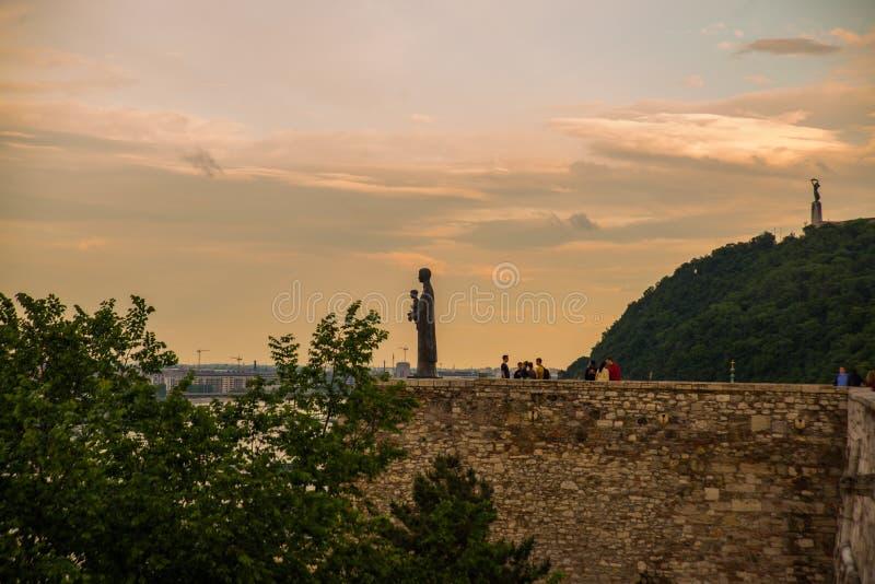 Budapest, Węgry: Rzeźba St Maria mater dei na wzgórze wierzchołku Buda kasztel Swobody statuy lub wolności statuy stojaki dalej zdjęcie stock