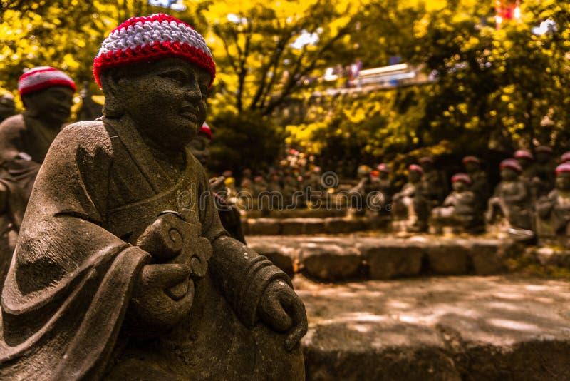 Buddah向道路由此守卫的雕塑扔石头 图库摄影
