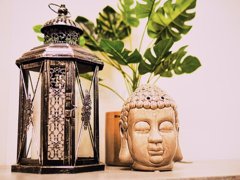 Buddah statua w nowożytnym domu, Domowa dekoracja Świeczki Buddha i zapalniczki Kierownicza statua i Monstera liście Wakacje deko obrazy royalty free
