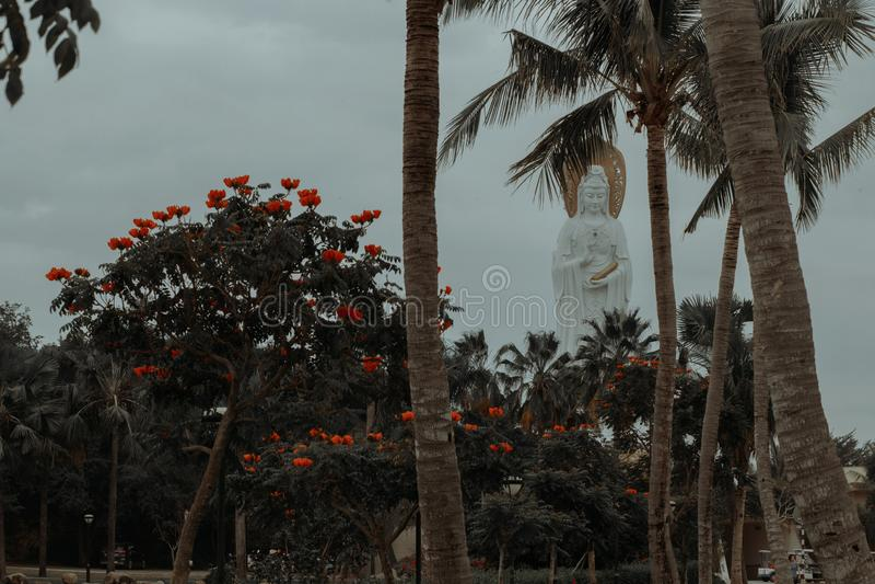 Buddah-Statuenansicht durch Bäume mit Blumen lizenzfreies stockbild
