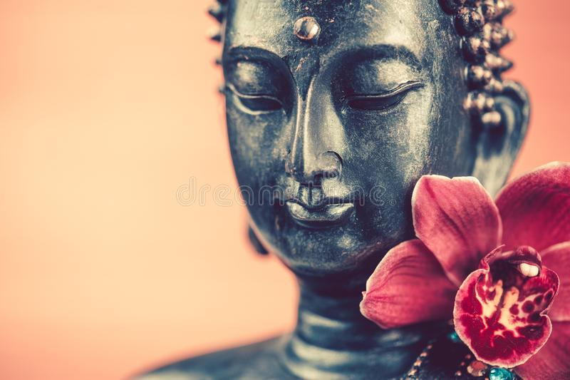 Buddha's head and orchid flower stock photo