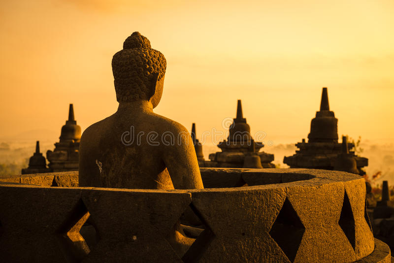 Buddha in Borobudur Temple at sunrise. Indonesia. Buddha statue in open stupa in Borobudur, or Barabudur, temple Jogjakarta, Java, Indonesia at sunrise. It is a stock photos