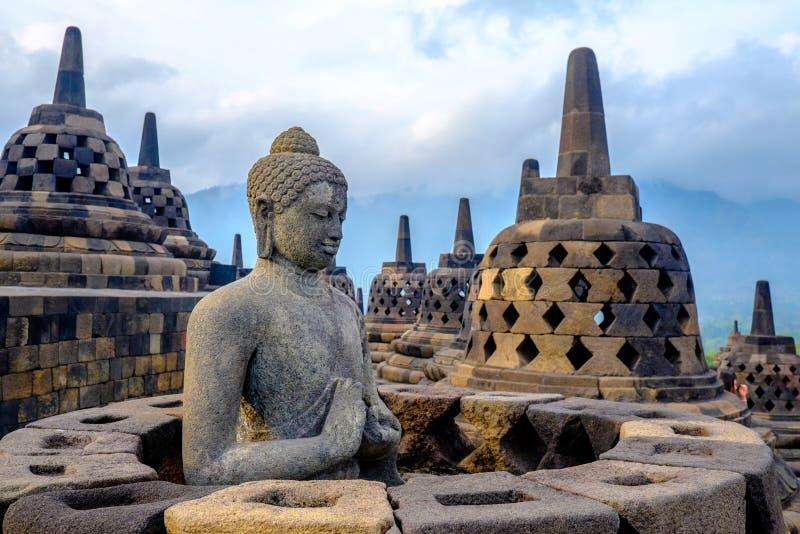 Buddha at Borobudur, Yogyakarta, Indonesia. This statue of Lord Buddha, nestled among 72 mini stupas at the Borobudur temple, has gazed serenely and benignly at stock photography