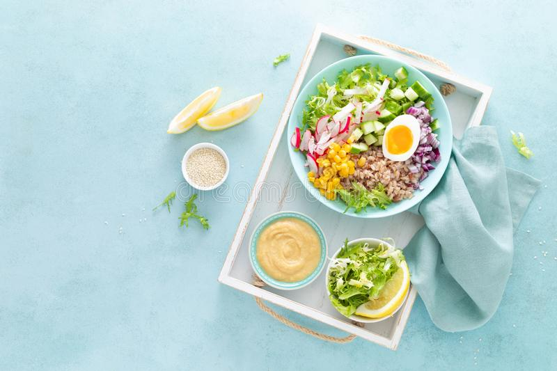 Buddha bowl with boiled egg, rice and vegetable salad of fresh lettuce, radish, cucumber, corn, onion and sesame seeds stock image