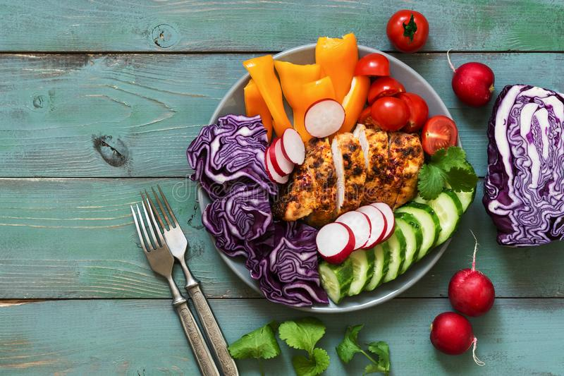 Buddha bowl, chicken breast baked with spices, fresh vegetables, blue rustic background. Top view, copy space. stock images