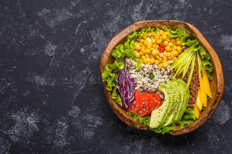 Buddha bowl with chickpea, avocado, wild rice, quinoa seeds, bell pepper, tomatoes, greens, cabbage, lettuce on dark stone table. royalty free stock images
