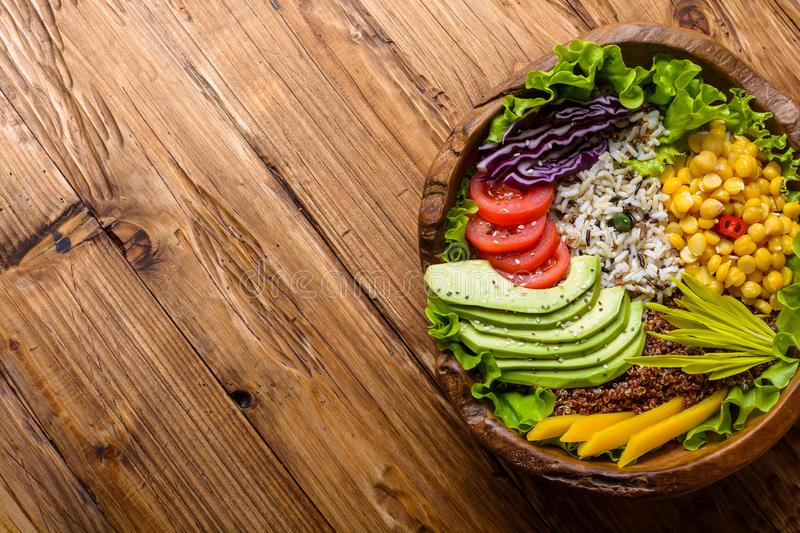 Buddha bowl with chickpea, avocado, wild rice, quinoa seeds, bell pepper, tomatoes, greens, cabbage, lettuce on old wooden table. royalty free stock images