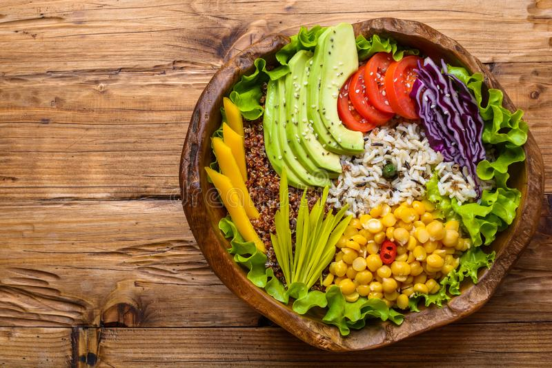 Buddha bowl with chickpea, avocado, wild rice, quinoa seeds, bell pepper, tomatoes, greens, cabbage, lettuce on old wooden table. stock photography