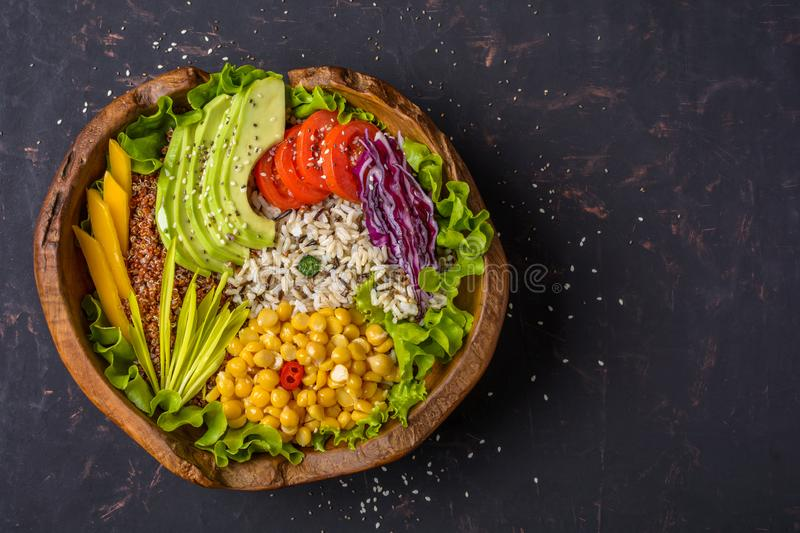 Buddha bowl with chickpea, avocado, wild rice, quinoa seeds, bell pepper, tomatoes, greens, cabbage, lettuce on shabby dark stone royalty free stock photography