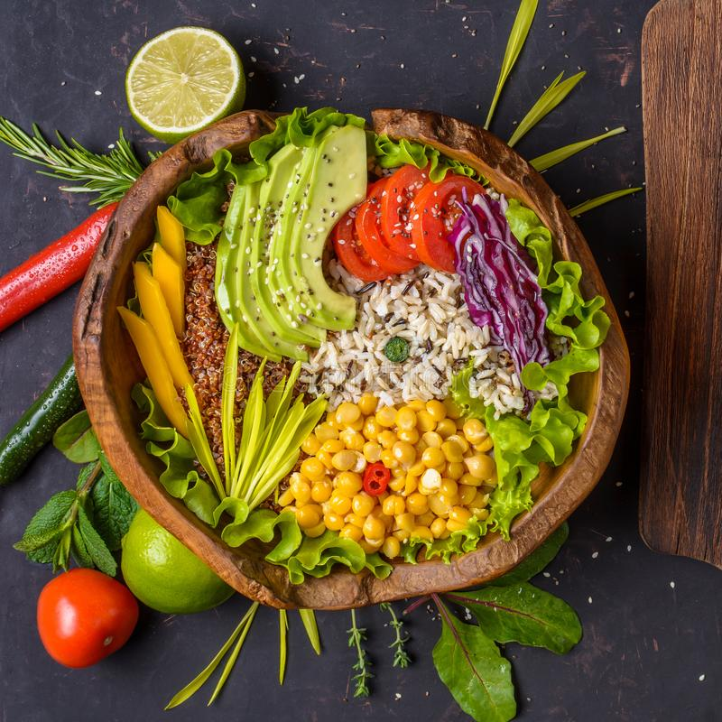 Buddha bowl with chickpea, avocado, wild rice, quinoa seeds, bell pepper, tomatoes, greens, cabbage, lettuce on shabby dark stone royalty free stock photos