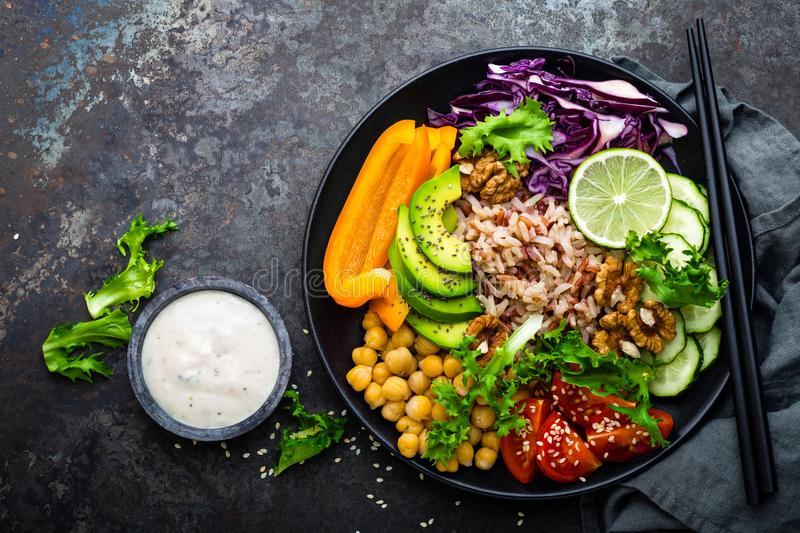 Buddha bowl dish with brown rice, avocado, pepper, tomato, cucumber, red cabbage, chickpea, fresh lettuce salad and walnuts. Healt stock image