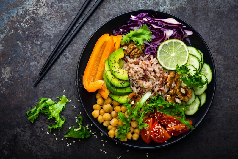 Buddha bowl dish with brown rice, avocado, pepper, tomato, cucumber, red cabbage, chickpea, fresh lettuce salad and walnuts. Healt stock photography