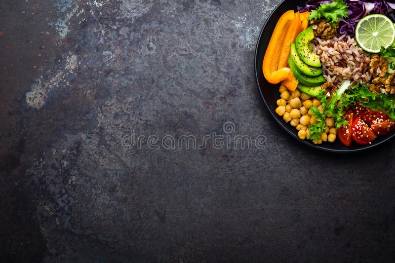 Buddha bowl dish with brown rice, avocado, pepper, tomato, cucumber, red cabbage, chickpea, fresh lettuce salad and walnuts. Healt royalty free stock photos