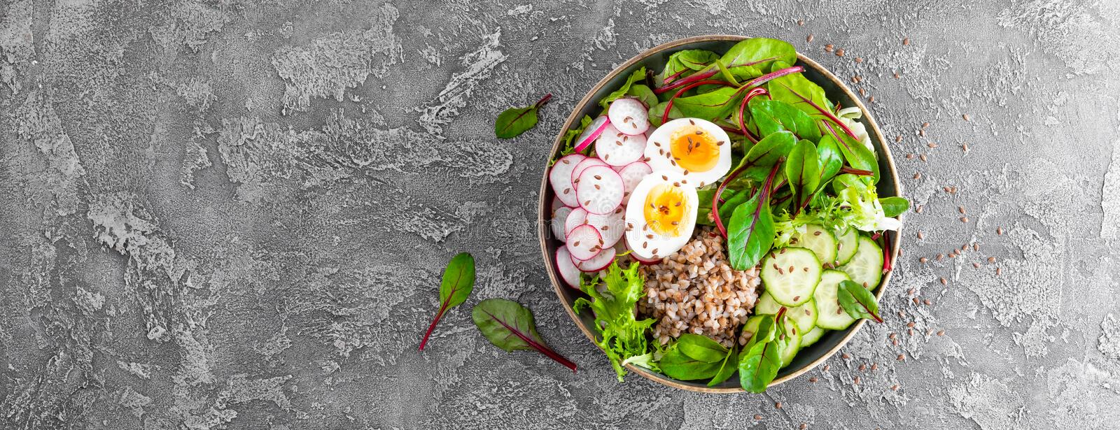 Buddha bowl dish with buckwheat porridge, boiled egg, fresh vegetable salad of radish, cucumber, lettuce and chard leaves. Healthy. Lunch menu. Top view. Banner stock image