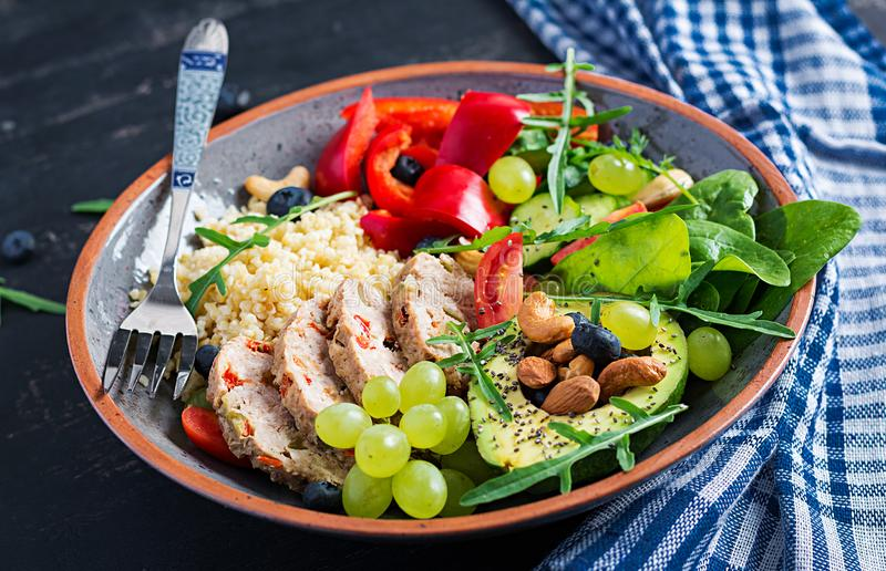 Buddha bowl dish with meatloaf, bulgur, avocado, sweet pepper, tomato, cucumber, berries and nuts. Detox and healthy superfoods bowl concept stock photography