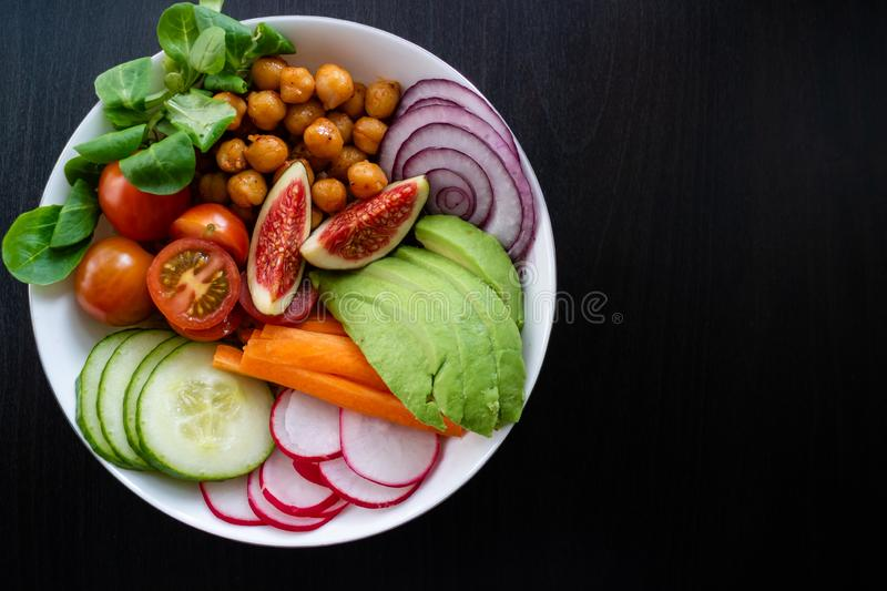 Buddha bowl with fresh vegetables on dark wooden background. Copy space. Vegan Buddha bowl made wit organic vegetables such as avocado, radish, cucumber, carrot stock images