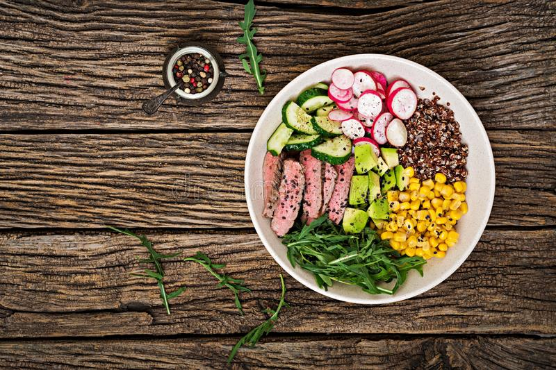 Buddha bowl lunch with grilled beef steak and quinoa, corn, avocado, cucumber royalty free stock photography