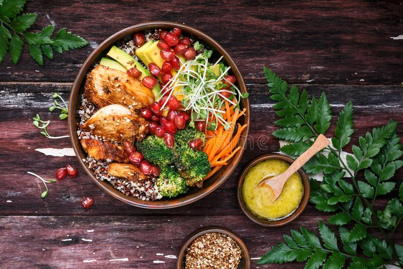 Buddha Bowl with Quinoa, Avocado, Roasted Chicken, Broccoli, Carrots and Turmeric Sauce stock images