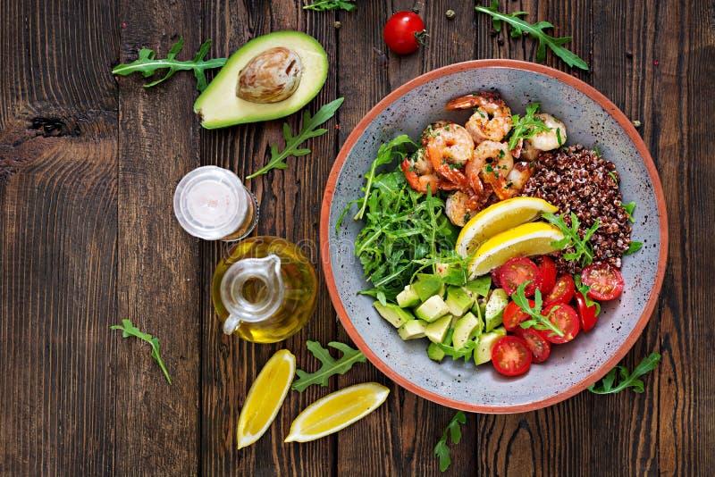 Buddha bowl with shrimps, tomato, avocado, quinoa, lemon and arugula stock photography