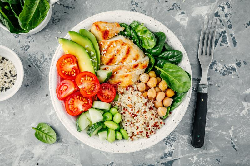 Buddha bowl with spinach salad, quinoa, roasted chickpeas, grilled chicken, avocado, tomatoes, cucumbers, sesame seeds. stock image