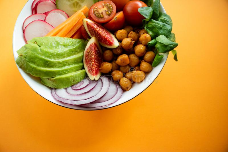 Buddha bowl wirh avocado, figs, chickpeas and carrot on orange background. Vegan Buddha bowl made wit organic vegetables such as avocado, radish, cucumber royalty free stock image