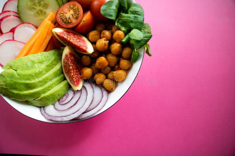 Buddha bowl wirh avocado, figs, chickpeas and carrot on pink background. Vegan Buddha bowl made wit organic vegetables such as avocado, radish, cucumber, carrot stock images