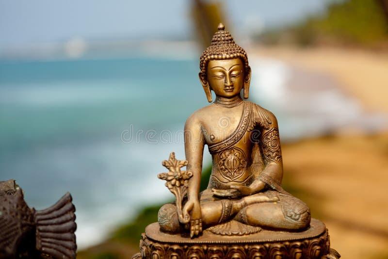 Buddha brass sculpture at ocean background. Indian brass sculpture at ocean background Kerala India stock photos