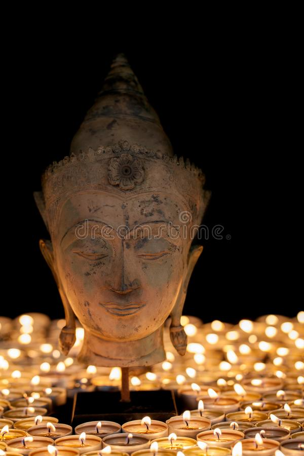 Buddha by candlelight. Enlightenment and mindfulness. Buddhist h. Ead statue. Beautiful calm zen buddhism portrait royalty free stock photography