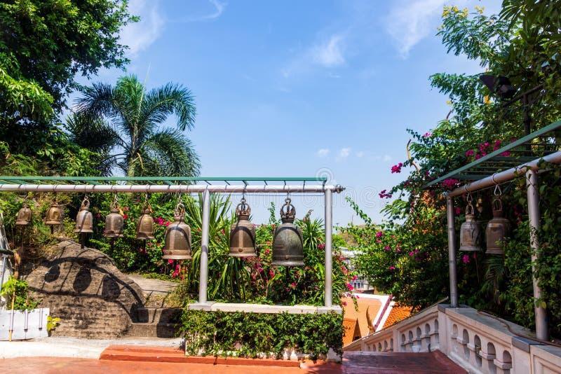 Buddha dzwony wiesza z rz?du otaczaj?cy zielonymi drzewami i kwiatami zdjęcie stock