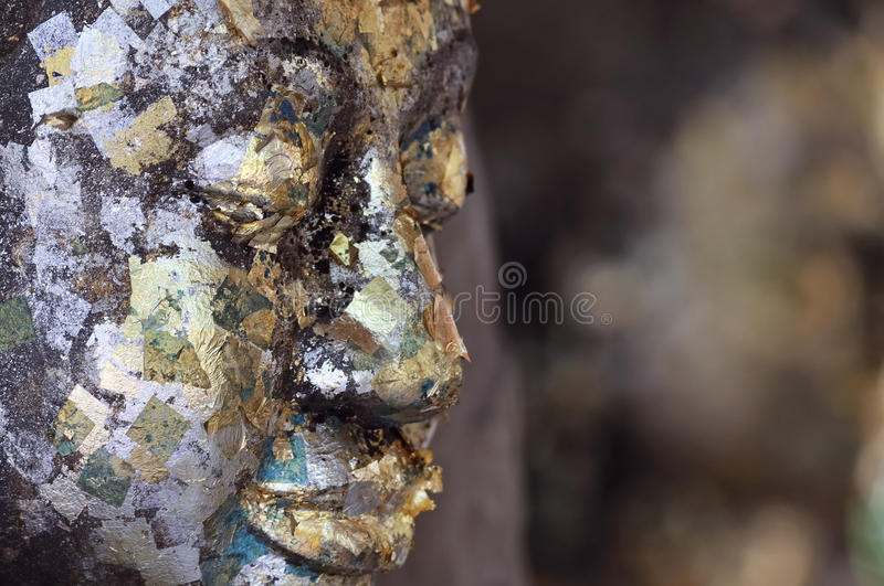 Buddha face covered with gold leaf stock images