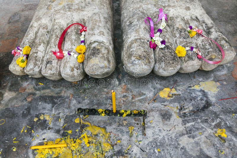 Buddha Feet in Sukhothai. Close up of Buddha Feet with Candles and Flowers in the Sukhothai Historical Park at Thailand stock photo