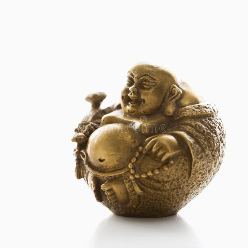 Buddha figurine. Happy laughing Buddha brass figurine on white background royalty free stock images