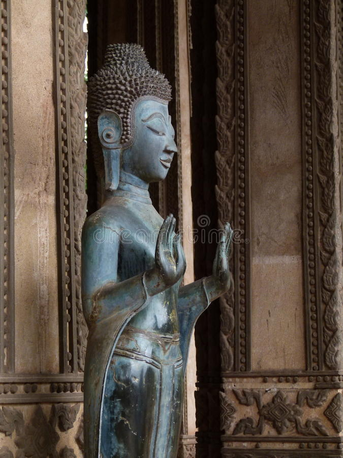 Buddha and hands in Laos. Wider photo of one of the many Buddhas in the temples of Laos. I photographed this one n the capital city of Vientiane royalty free stock images