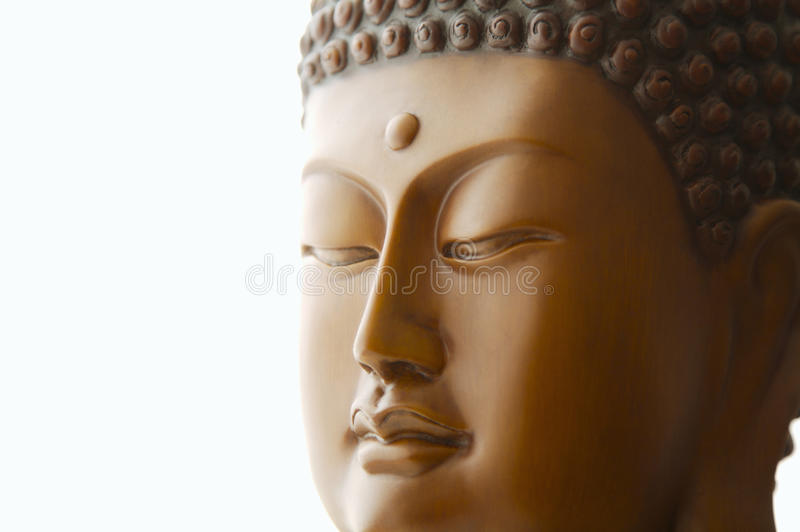 Buddha head carving against a white background stock photography